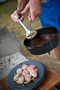 A man uses a ladle to add stock to a dish prepared in the lid of a dutch oven.