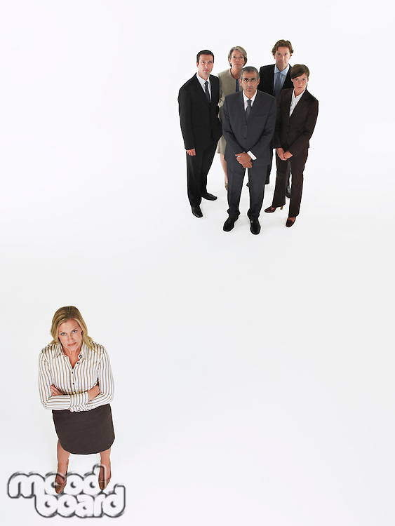 Businesswoman standing apart from group