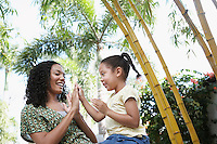 Girl (5-6 years) clapping hands with mother in forest low angle view