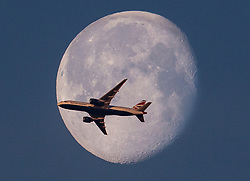 © Licensed to London News Pictures. 03/05/2018. London, UK. A British Airways airliner passes the setting moon as the weather improves ahead of the bank holiday weekend. Photo credit: Peter Macdiarmid/LNP