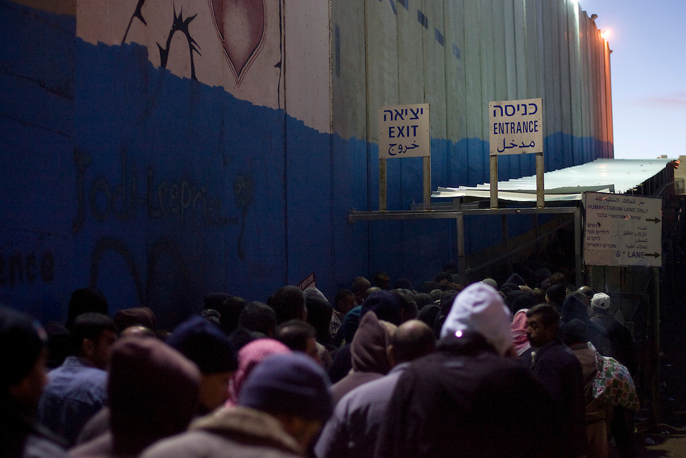 Palestinian workers queue along the separation wall at the checkpoint 300, the crossing passage between Bethleem and Jerusalem, on December 15. 2010 in Bethleem.Workers arrived every day at two o'clock in the morning  to catch a place at the entrance of the checkpoint, so they can arrived at time to their work in the Israeli side. Photo by Olivier Fitoussi