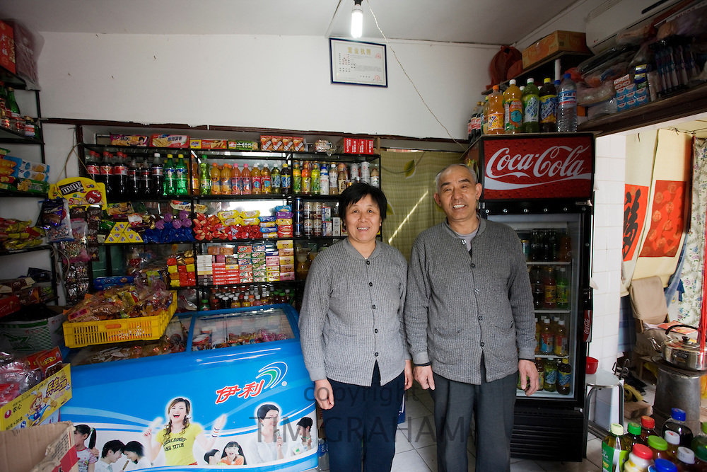 Shopkeepers in traditional shop for groceries, sweets and drinks, Hutongs Area, Beijing, China
