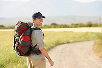 Hiker with backpack walking on country road