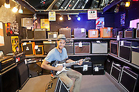 Portrait of happy young male customer strumming the guitar in music store