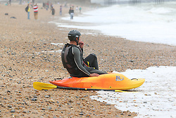 © Licensed to London News Pictures. 04/07/2014. Brighton, UK. A man in a Kajak on Brighton Beach. Rain and clouds has stopped most people from visiting the South Coast while rough seas dettered people from swimming. Photo credit : Hugo Michiels/LNP