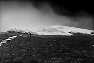 Lone Kichwa man descends from one of the glacier running down from the summit of Cotopaxi Volcano [5,897 m (19,347 ft)] at about 5,000 meters elevation, considered by some to be the world's highest active volcano.  Ecuador.  As important as the volcanoes raw power, its glaciers are one of the primary sources feeding the vast river system of the Amazon Basin.<br /> <br /> Cotopaxi is believed to mean &quot;Neck of the Moon&quot; and has been considered a sacred mountain since before Inca times.<br /> Scientists say that Cotopaxi has lost 40% of its glacier cover since 1976.  Cotopaxi is one of the sources for the Amazon Watershed.  Its glaciers are sources to the Rio Napo and Rio Pastaza, which in turn feed the mighty Amazon River.