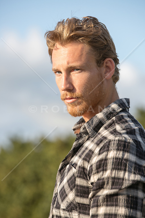portrait of a rugged and handsome man with a beard at sunset