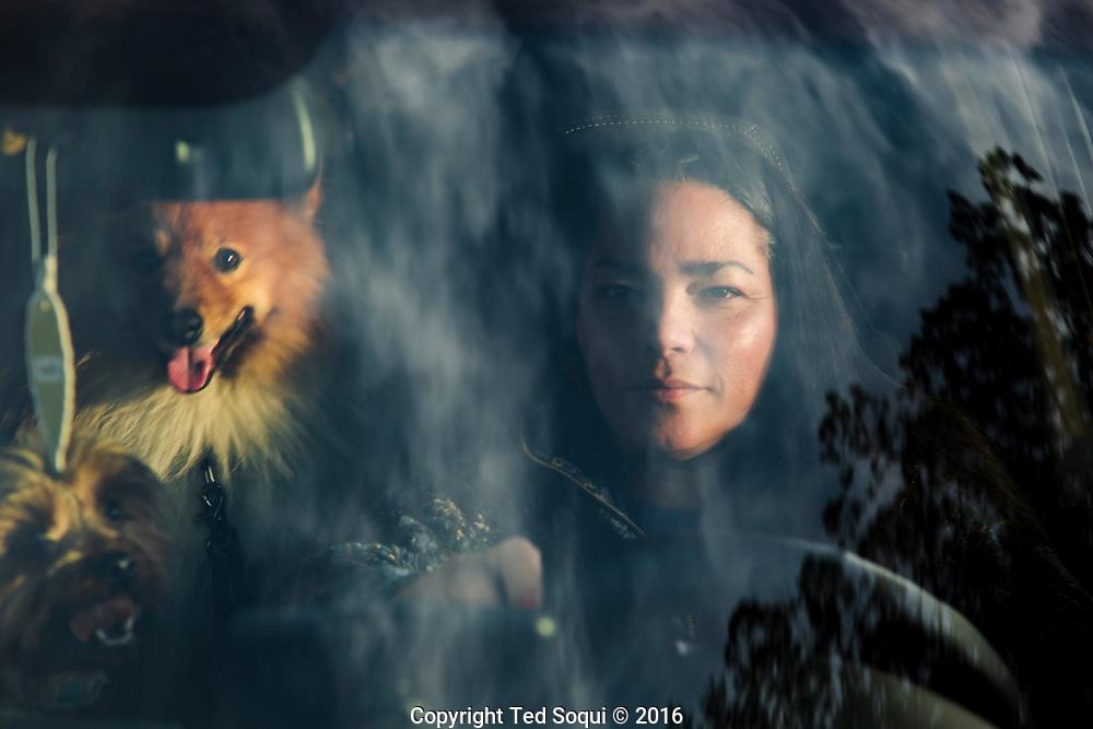 Migdalia Vasquez with her 4 dogs and two birds. <br /> She lives inside her car, a Kia Soul. Santa Rosa, CA.