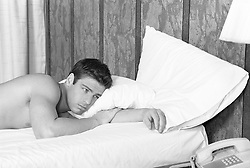 Young man lying on his bed looking thoughtfully at his telephone, (b&w)