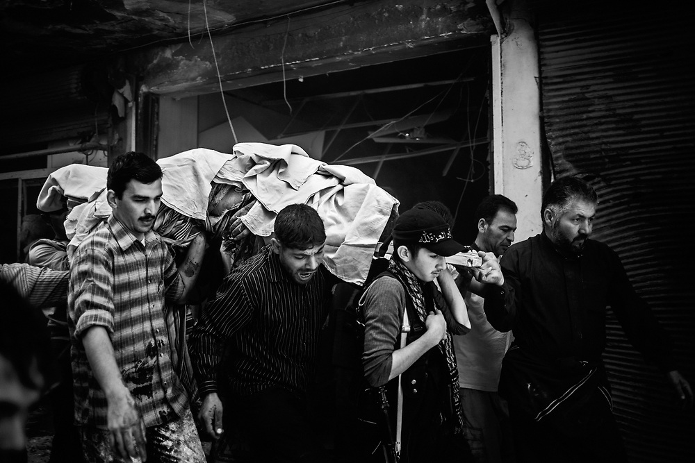 Syria, Aleppo, 2012/10/13.<br /> At 9:18 AM, Assad loyalist forces shell two buildings using helicopter rockects in the Shaar discrict. The body of a man who died in the explosion of his shop, taken to a taxi that will transport him to the hospital for the recognition.