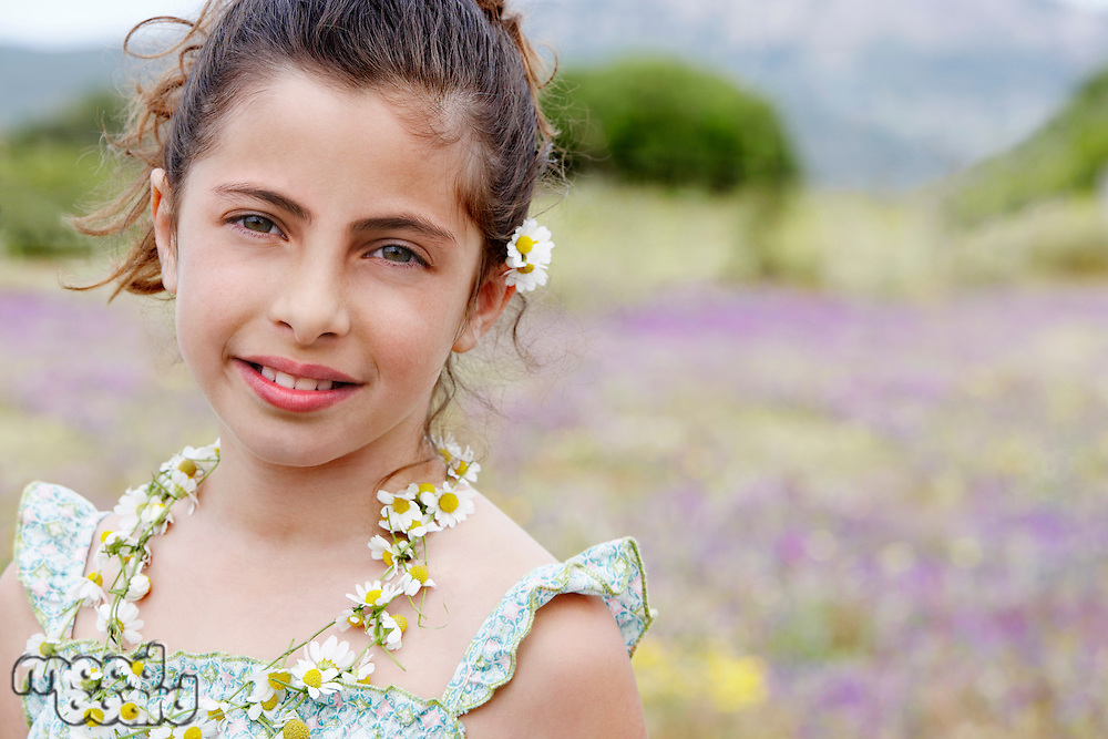 Smiling Pre-teen wearing necklace of flowers in field of flowers