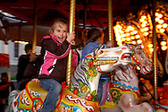 McKenzie Brooks, 4, of Vandalia takes a spin on the carousel, part of the 'Street Fair on Third' during the Grande Illumination & Dayton Children's Parade Spectacular in Lights which begins the 39th Annual Dayton Holiday Festival in Courthouse Square in downtown Dayton, Friday, November 25, 2011.