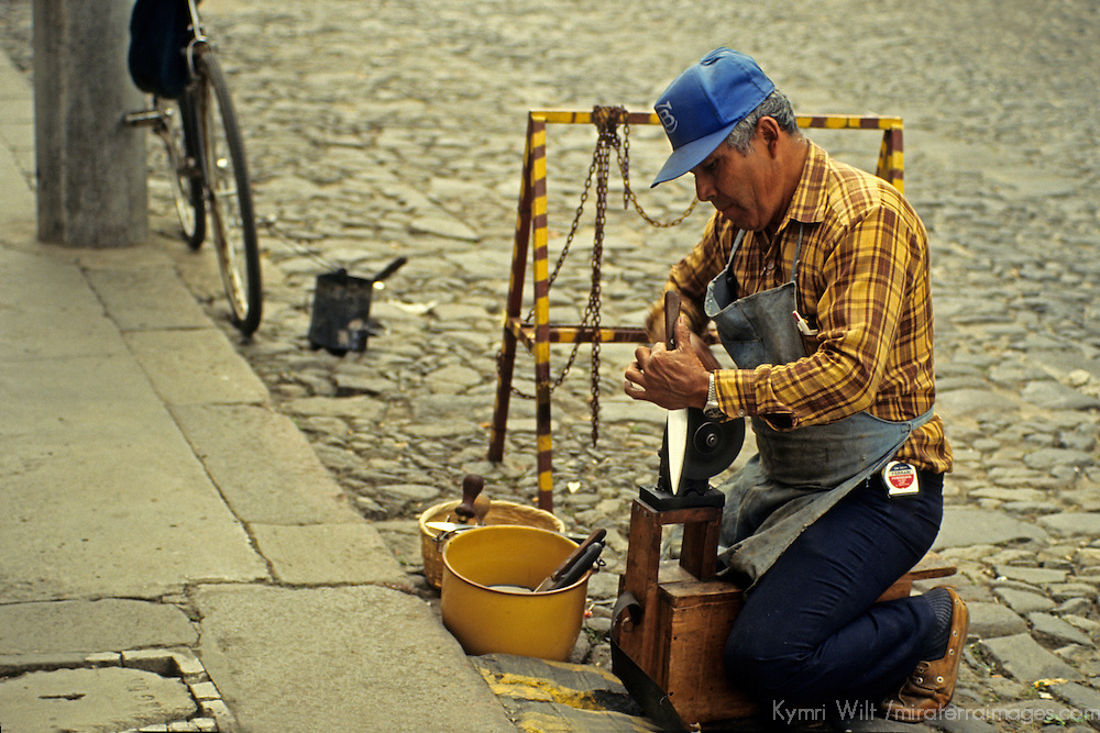 Central America, Guatemala, Antigua. A Guatemalan tradesman sharpens knives curbside in Antigua, Guatemala.