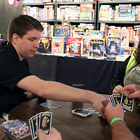 Organizer of Tupelo Game Days Derek Harris, left, shows attendees how to play a card game called Drunken Goats