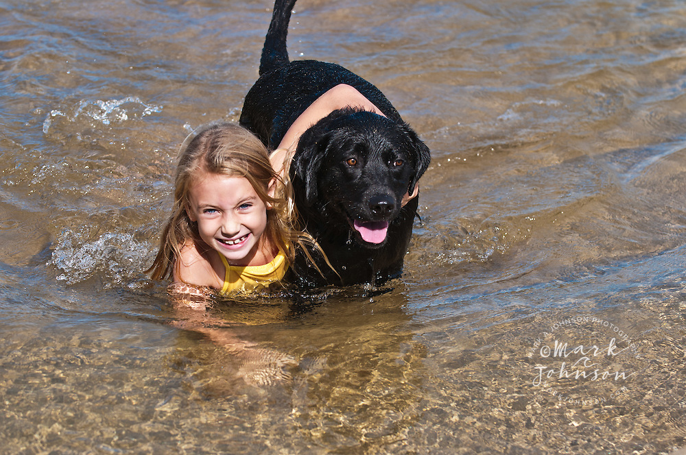 Girl playing with her black labrador dog at the beach