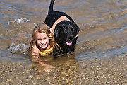 Girl playing with her black labrador dog at the beach *****Property Release available ****Model Release available
