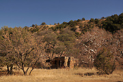 An abandoned gold mine camp cabin constructed from rock sits along a creek in the Santa Rita Mountains, Coronado National Forest, Sonoran Desert, Sonoita, Arizona, USA.