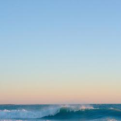 Single wave breaks on beach at sunset. Boca Grande beach Florida, USA.