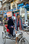 Street scene in holy city of Varanasi, young muslim woman in black burkha rides in rickshaw, Benares, Northern India