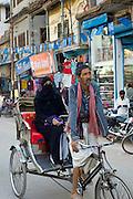 Street scene in holy city of Varanasi, young muslim woman in black burkha rides in rickshaw, Benares, Northern India