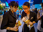 12 AUGUST 2018 - BANGKOK, THAILAND: Mall employees light candles before a candlighting ceremony to honor the 86th birthday of Sirikit, the Queen Mother of Thailand at EmQuartier Mall in Bangkok. She was the wife of Bhumibol Adulyadej, the late King, and she is the mother of His Majesty King Maha Vajiralongkorn Bodindradebayavarangkun of Thailand, who succeeded his father. August 12 is also celebrated as Mother's Day in Thailand.    PHOTO BY JACK KURTZ