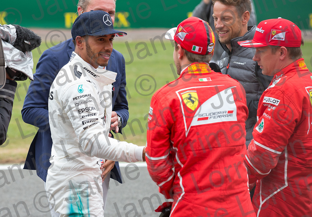 The 2017 Formula 1 Rolex British Grand Prix at Silverstone Circuit, Northamptonshire.<br /> <br /> Pictured: Mercedes AMG Petronas Driver Lewis Hamilton shakes hands with Sebastian Vettel as Kimi Raikkonen, David Coulthard and Jenson Button look on at the British F1 Grand Prix.<br /> <br /> Jamie Lorriman<br /> mail@jamielorriman.co.uk<br /> www.jamielorriman.co.uk<br /> +44 7718 900288