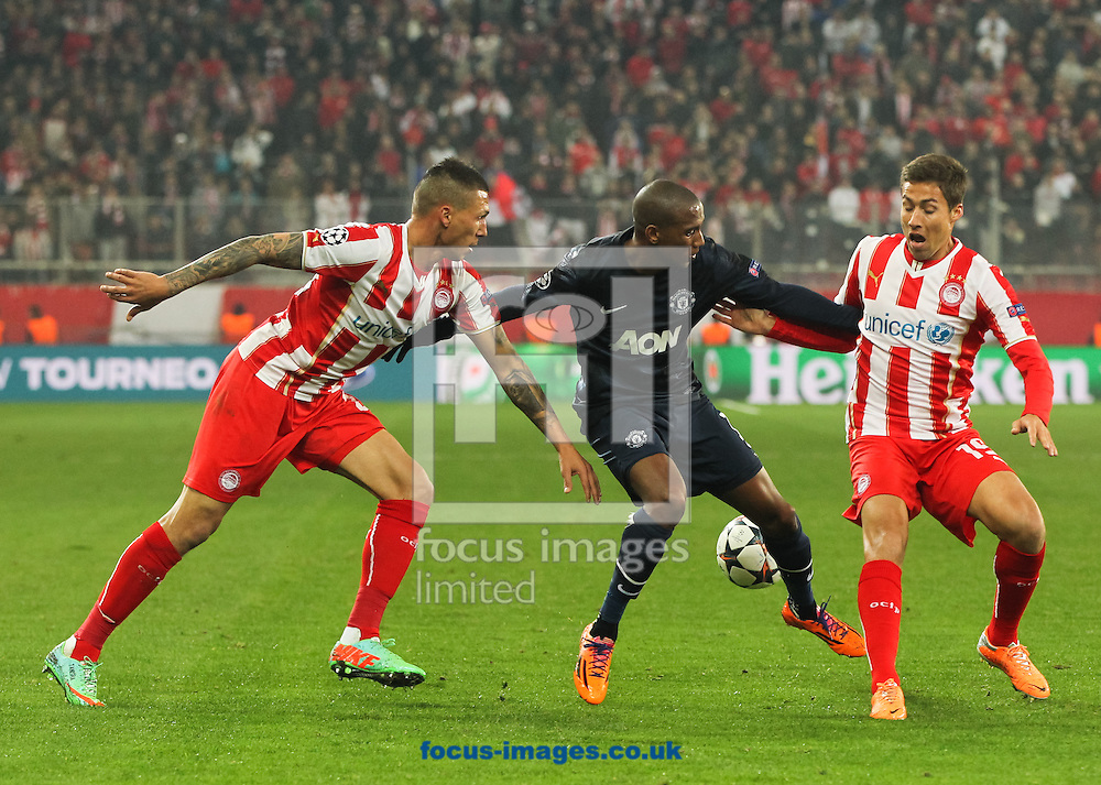 Jos&eacute; Holebas (left) and David Fuster (right) of Olympiacos F.C. try to get the ball off of Ashley Young (centre) of Manchester United during the UEFA Champions League match at Karaiskakis Stadium, Piraeus<br /> Picture by Tom Smith/Focus Images Ltd 07545141164<br /> 25/02/2014