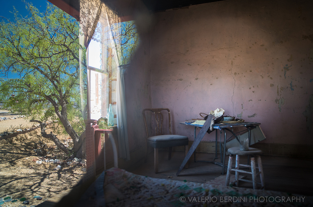 Caught through a window reflecting the landscape outside, the remains of a table, stall and a jigsaw inside a room in an abandoned house in the ghost town of Ryolite in the Death Valley. Nevada, USA.