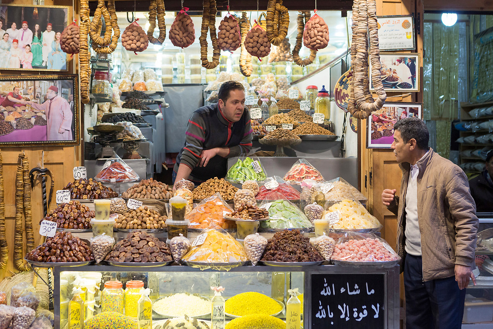 FEZ, MOROCCO - 1st FEBRUARY 2018 Market vendor and customer chat at a dried fruit and nuts market stall in the old Fez Medina, Middle Atlas Mountains, Morocco.