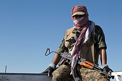 © Licensed to London News Pictures. 11/12/2014. Sinjar Mountains, Iraq. A Yazidi fighter sits on the side of a truck during a trip to pick up supplies dropped by Iraqi Air Force Mi-17 Hip helicopters onto Mount Sinjar.<br /> <br /> Although a well publicised exodus of Yazidi refugees took place from Mount Sinjar in August 2014 many still remain on top of the 75 km long ridge-line, with estimates varying from 2000-8000 people, after a corridor kept open by Syrian-Kurdish YPG fighters collapsed during an Islamic State offensive. The mountain is now surrounded on all sides with winter closing in, the only chance of escape or supply being by Iraqi Air Force helicopters. Photo credit: Matt Cetti-Roberts/LNP