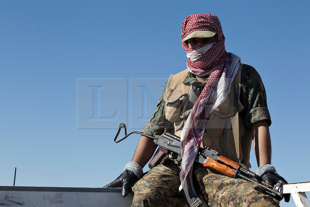 &copy; Licensed to London News Pictures. 11/12/2014. Sinjar Mountains, Iraq. A Yazidi fighter sits on the side of a truck during a trip to pick up supplies dropped by Iraqi Air Force Mi-17 Hip helicopters onto Mount Sinjar.<br /> <br /> Although a well publicised exodus of Yazidi refugees took place from Mount Sinjar in August 2014 many still remain on top of the 75 km long ridge-line, with estimates varying from 2000-8000 people, after a corridor kept open by Syrian-Kurdish YPG fighters collapsed during an Islamic State offensive. The mountain is now surrounded on all sides with winter closing in, the only chance of escape or supply being by Iraqi Air Force helicopters. Photo credit: Matt Cetti-Roberts/LNP