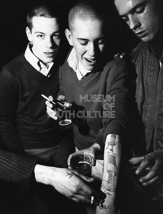 Three skinheads, drinking, showing a 'Kill Mods' tattoo, UK, 1980's.