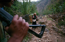 "RUKUM DISTRICT, NEPAL, APRIL 20, 2004:  A woman passes a Maoist guerilla carrying grass for her cattle   in Rukum district April 20, 2004.  In their remote strongholds, the Maoists collect taxes from the villagers and have set up civil administrations, and ""people's courts"" to settle rows. They also raise money by taxing villagers and foreign trekkers. Though young, they are fearsome fighters and  specialise in night attacks and hit-and-run raids. They are tough in Nepal's rugged terrain, full of thick forests and deep ravines and the 150,000 government soldiers are not enough to combat this growing movement that models itself after the Shining Path of Peru. (Ami Vitale/Getty Images)"