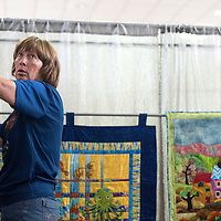 Mattila Ann hangs a quilt in one of the booths at the Grants Community Center Thursday in preparation of the weekend showcase.