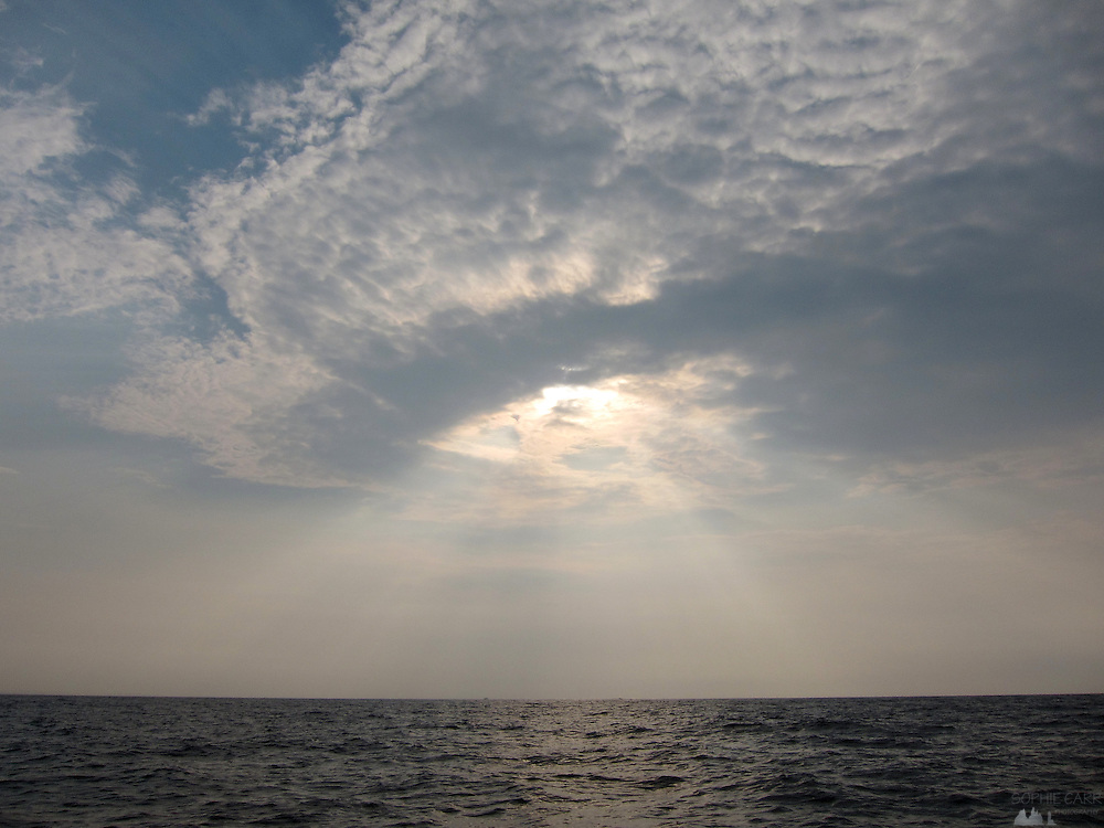Sun shines through patchy clouds over the sea off the coast at Mirissa in southern Sri Lanka, in the early morning