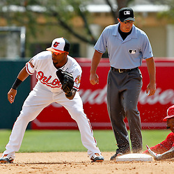 March 20, 2012; Sarasota, FL, USA; Philadelphia Phillies third baseman Michael Martinez (7) slides in for a double past Baltimore Orioles second baseman Robert Andino (11) during the XXXX inning of a spring training game at Ed Smith Stadium.  Mandatory Credit: Derick E. Hingle-US PRESSWIRE