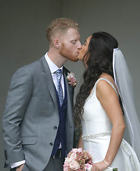 England all-rounder Ben Stokes kisses his newly married wife Clare, out side St Mary the Virgin, East Brent, Somerset.