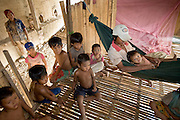 30 JUNE 2006 - PHNOM PENH, CAMBODIA: The children of brick factory workers in a hut at a brick factory in Phnom Penh, Cambodia. This particular factory employs about 30 people. The live on the premises with their families. Most of the workers migrated to Phnom Penh from the countryside looking for better paying jobs than they could find in the countryside. According the United Nations Food and Agricultural Organization, there are more than 70 brick factories in Phnom Penh and its environs. Environmentalists are concerned that the factories, most of which burn wood in their kilns, contribute to deforestation in Cambodia. They are encouraging factory owners to switch to burning rice husks, as brick kilns in neighboring Vietnam do. The brick factories are kept busy feeding Phnom Penh's nearly insatiable appetite for building materials as the city is in the midst of a building boom brought by on economic development and the need for new office complexes and tourist hotels.   Photo by Jack Kurtz / ZUMA Press