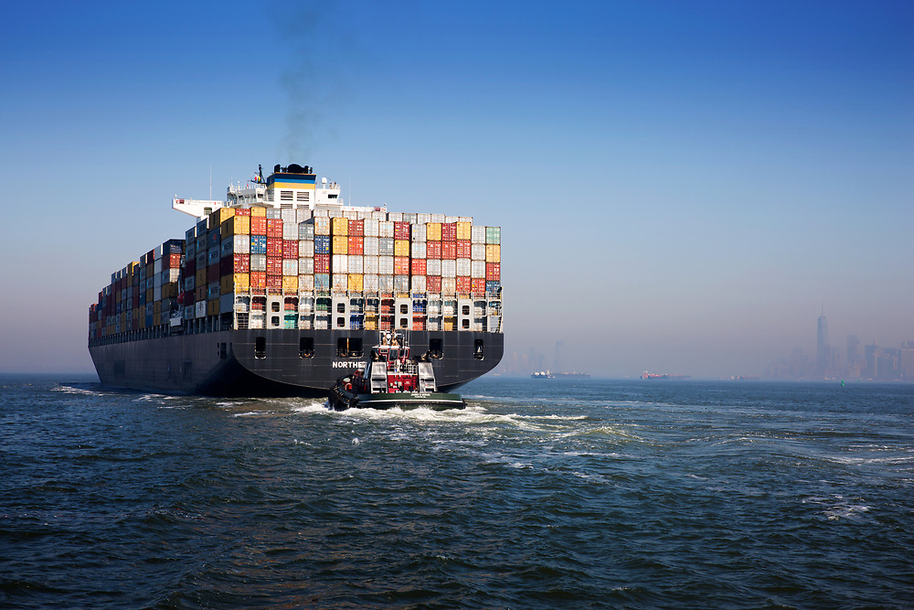 A Moran tug bringing in a cargo ship into the NYC harbor port