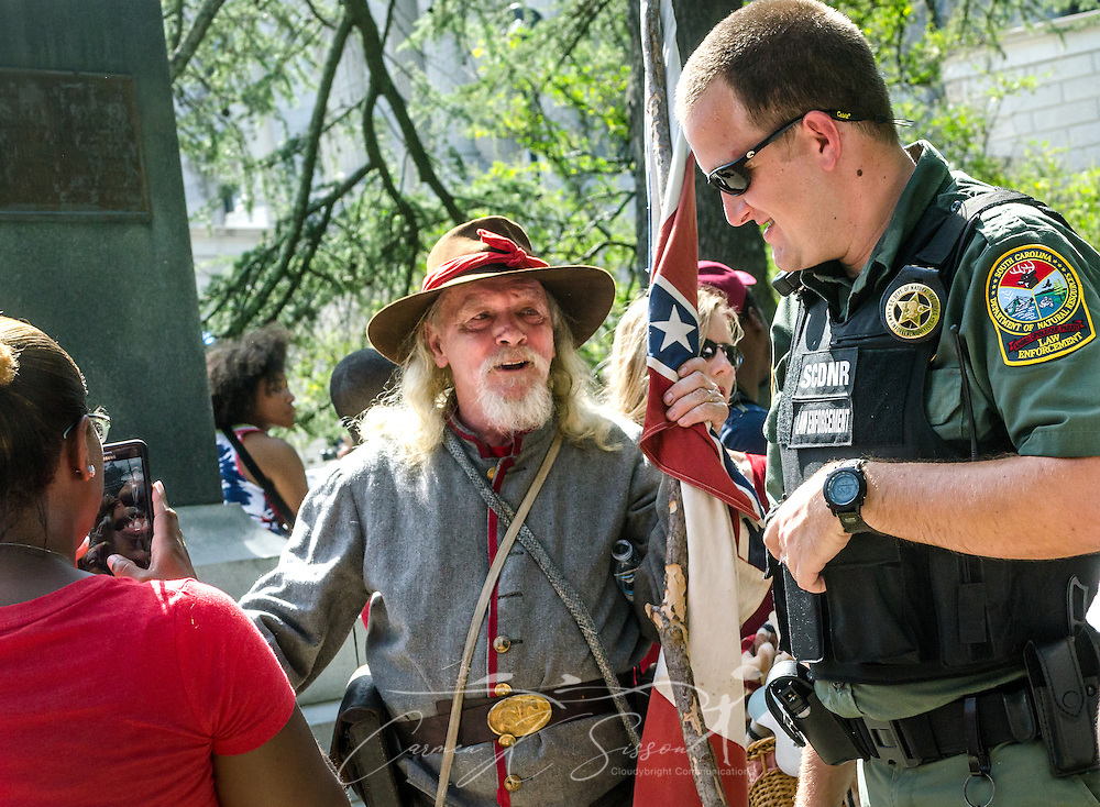 A man dressed as a Confederate soldier and carrying a Confederate flag talks with an officer with the South Carolina Department of Natural Resources, July 10, 2015, in Columbia, S.C. Thousands flocked to the South Carolina Statehouse to see the removal of the  Confederate flag. The flag flew above the capitol dome from 1961-2000, then was moved to the grounds. The flag, which is now permanently removed, will be stored at the Confederate Relic Room and Military Museum. The House voted for its removal after the shooting of nine African-Americans at Emanuel African Methodist Episcopal Church in Charleston, June 17, 2015. Alleged shooter Dylann Roof, who published a manifesto on his website supporting white supremacist beliefs, was seen in numerous photographs holding the Confederate flag. (Photo by Carmen K. Sisson/Cloudybright)
