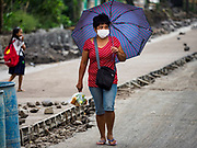 "22 JANUARY 2018 - GUINOBATAN, ALBAY, PHILIPPINES:  A woman in Guinobatan wears a face mask while she walks home from shopping. Several communities in Guinobatan were hit ash falls from the eruptions of the Mayon volcano and many people wore face masks to protect themselves from the ash. There were a series of eruptions on the Mayon volcano near Legazpi Monday. The eruptions started Sunday night and continued through the day. At about midday the volcano sent a plume of ash and smoke towering over Camalig, the largest municipality near the volcano. The Philippine Institute of Volcanology and Seismology (PHIVOLCS) extended the six kilometer danger zone to eight kilometers and raised the alert level from three to four. This is the first time the alert level has been at four since 2009. A level four alert means a ""Hazardous Eruption is Imminent"" and there is ""intense unrest"" in the volcano. The Mayon volcano is the most active volcano in the Philippines. Sunday and Monday's eruptions caused ash falls in several communities but there were no known injuries.   PHOTO BY JACK KURTZ"