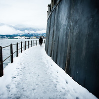 Man alone in long black coat walking along a snow covered path with fence along ocean. Large wall on right side, industrial site in background.