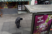 An elderly lady is bent from back problems on the Walworth Road in Southwark, on 4th April 2019, in London, England.
