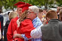 Graduate receives a congratulatory hug after commencement.