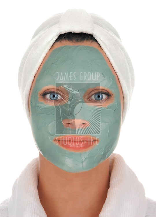 front view of a beautiful young woman in white terry cloth bathrobe and turban with deep sea mud mask treatment on white background