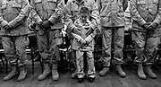 Bronze Star Recipient SFC Mark Rizzo,  holding his son Giavanni, 7, says a prayer.  Soldiers from B Battery, 3rd Battalion 112 Field Artillery were welcomed home with a parade and ceremony at the Lawrenceville Armory on February 11, 2005.