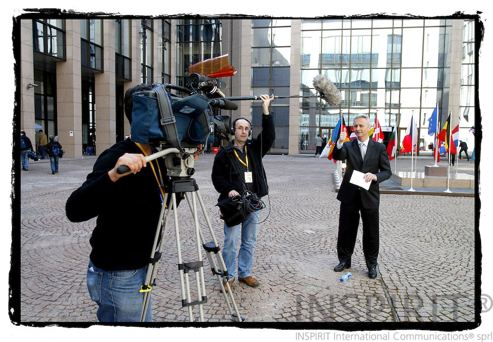 BRUSSELS - BELGIUM - 22 MARCH 2005 --A TV cameraman, soundman and journalist waiting for duing their story for TV in the yard with international flags of the EU Council during a Summit.--  PHOTO: ERIK LUNTANG / INSPIRIT Photo