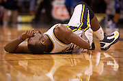 Jazz center Al Jefferson winces in pain and grabs his back during the second half of the NBA basketball game between the Utah Jazz and the Orlando Magic at Energy Solutions Arena, Wednesday, Dec. 5, 2012.