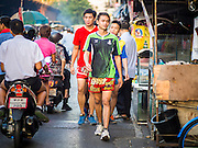 """11 DECEMBER 2014 - THONBURI, BANGKOK, THAILAND:  Boxers from the Kanisorn gym work out in front of the gym. The Kanisorn boxing gym is a small gym along the Wong Wian Yai - Samut Sakhon train tracks. Young people from the nearby communities come to the gym to learn Thai boxing. Muay Thai (Muai Thai) is a Thai fighting sport that uses stand-up striking along with various clinching techniques. It is sometimes known as """"the art of eight limbs"""" because it is characterized by the combined use of fists, elbows, knees, shins, being associated with a good physical preparation that makes a full-contact fighter very efficient. Muay Thai became widespread internationally in the twentieth century, when practitioners defeated notable practitioners of other martial arts. A professional league is governed by the World Muay Thai Council. Muay Thai is frequently seen as a way out of poverty for young Thais and Muay Thai camps and schools are frequently crowded. Muay Thai professionals and champions are often celebrities in Thailand.    PHOTO BY JACK KURTZ"""