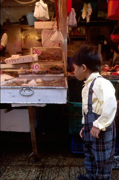 A young boy checks out fish for sale at the wet market, Hong Kong, China.